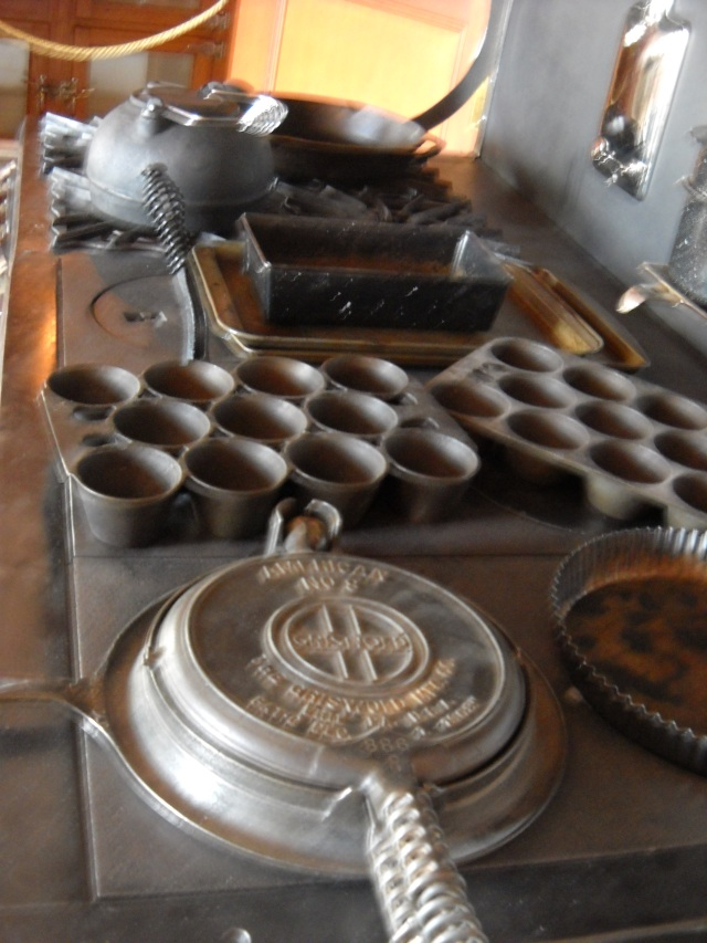 A waffle iron, tart dish, and muffin pans sitting on the stove top